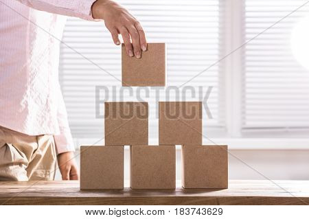Close-up Of A Woman Placing Block On Desk