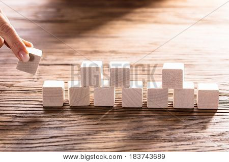 Close-up Of A Person Hand Arranging Blocks On Wooden Desk