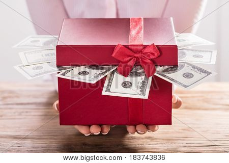 Close-up Of A Woman Holding Gift Box Of Us Dollar Bills