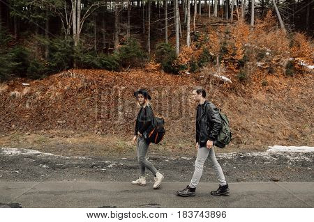 the couple are traveling. Boy and girl with backpacks travel. The couple is on the road. The girl looks up. Girl goes for a man.