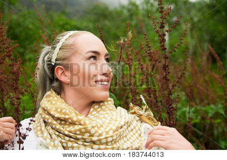 Close up portrait of smiling beautiful woman enjoying nature in a forest