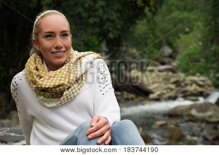 Happy young girl sitting by the river rocks in a forest enjoying the quietness