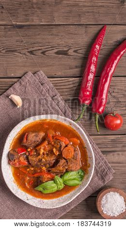 Bowl of goulash on rustic wooden  background. Traditional hungarian meal,  beef stew. Vertical.Toned. Copy space