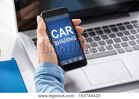 Close-up Of A Woman Using Car Sharing Service On Smart Phone