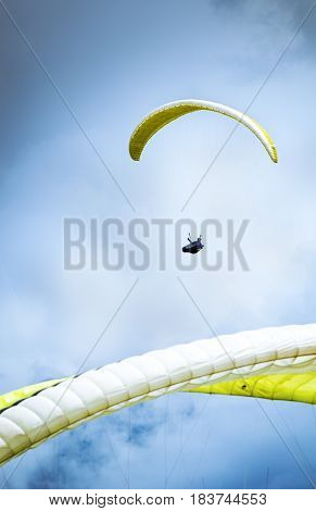 Two paragliders flying in cloudy weather. Paragliding
