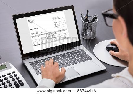 Close-up Of A Businesswoman Calculating Invoice On Laptop In Office