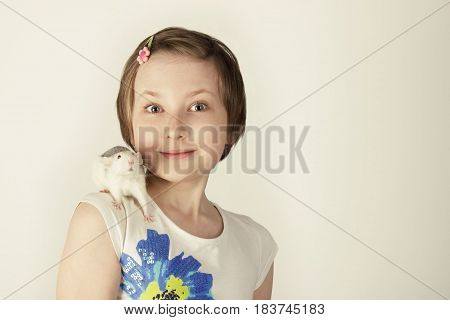People and pet concept - Close-up portrait of an adorable smiling girl with her pet rat on white. Cropped shot of teen girl with rat, on white.Child and pet on white.