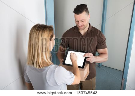 View Of A Young Woman Signing After Receiving Box From Delivery Man