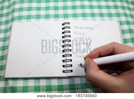 Hand with pencil writing shopping grocery list