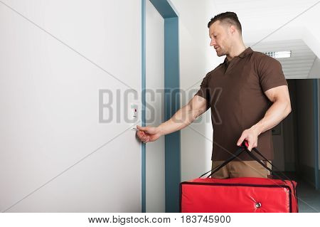 Close-up Of A Young Pizza Delivery Man Ringing The Door Bell