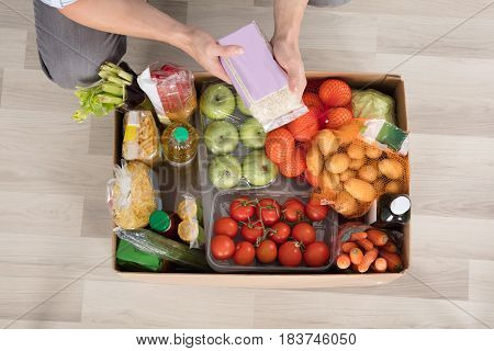 Overhead View Of A Man Checking The Groceries In The Cardboard Box