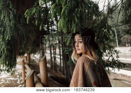 woman is dressed in a poncho. Woman in black hat. Walk in the woods. Photo shoot in the woods.