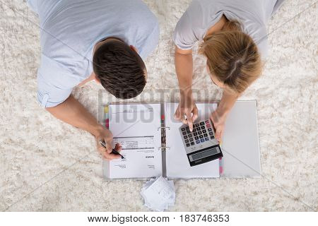 Elevated View Of Young Couple Lying On Carpet Calculating Their Bills Using Calculator