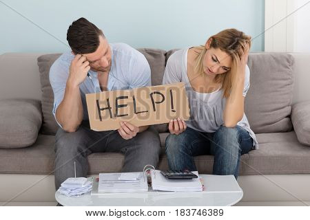 Worried Young Couple Sitting On Couch Holding Help Sign While Calculating Bills At Home