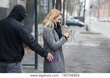 Man In A Hood Stealing Purse From Woman's Coat Pocket On Street poster