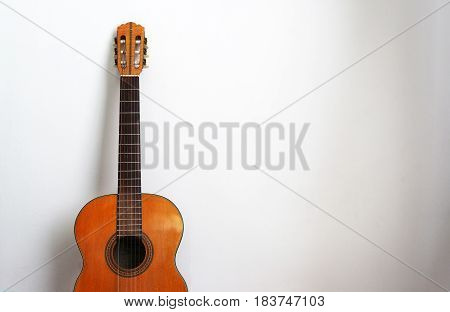 Acoustic guitar on a white wall background