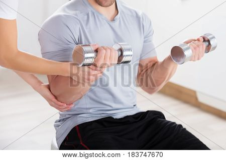 Close-up Of Instructor Assisting Man For Exercising With Dumbbell