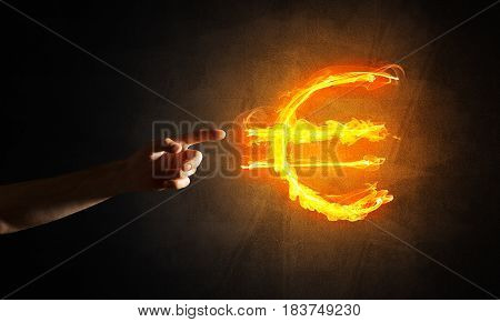 Close of man hands pointing at fire glowing euro sign