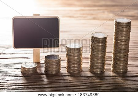 Blank Small Chalk Board With Increasing Coin Stack On Wooden Table