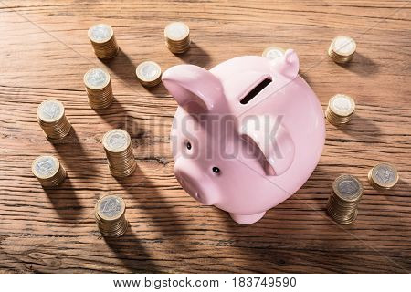Elevated View Of A Piggybank Surrounded With Coin Stacks On Wooden Table