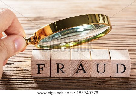 A Person Examining Fraud Blocks Through Magnifying Glass On Wooden Table