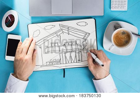 Overhead View Of A Businessman Drawing House On Checkered Notebook At Workplace