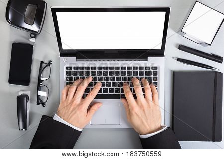 Elevated View Of A Businessperson Using Laptop On Office Desk