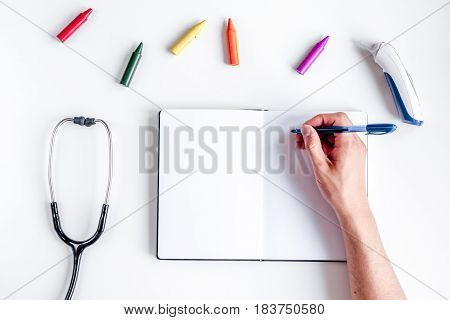 Pediatrics equipment with crayons, copybook, stethoscope on white table background top view space for text