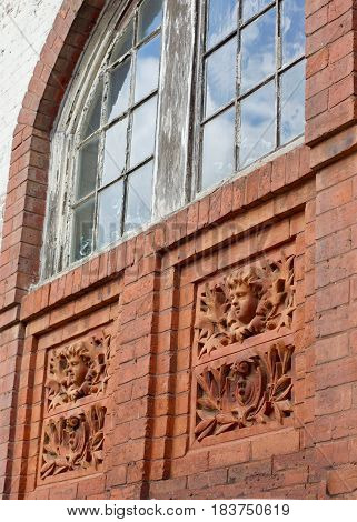 Old brick building window with weathered woods, chipping paint and two inset reliefs with floral and face carvings