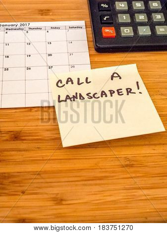 calendar, calculator and post it note regarding landscaping