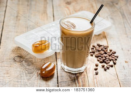 cold coffee glass with ice cubes for cafe menu on wooden table background