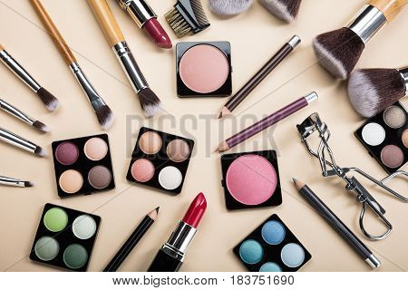 Elevated View Of Various Makeup Brushes And Make-up Products On Beige Background