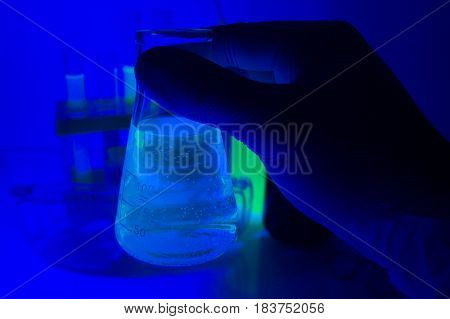 Hand in rubber gloves holding a laboratory bottle with glowing blue liquid in ultraviolet lights.