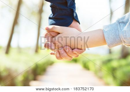 Road to life. Hands. Father's and his son hands. Dad leading son over summer nature outdoor. Male and children hands closep. Family, trust, protecting, care, parenting concept.