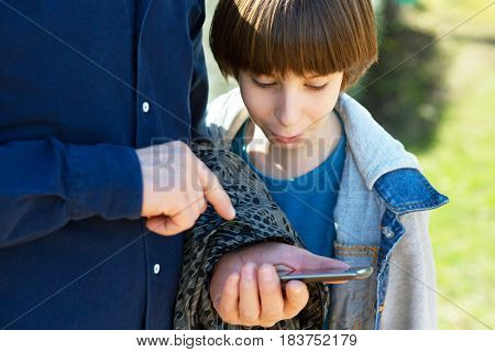 Father pointing at smartphone and boy looking with surprise and interest. Father with son using smart phone outdoor together. Young boy with his father in spring park.