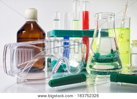 Photo composition of a laboratory bottles, test-tubes, protective glasses & medicine dropper laying on a white glass table.