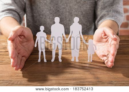 Close-up Of A Woman Protecting Family Of White Paper Cut Out On Wooden Desk