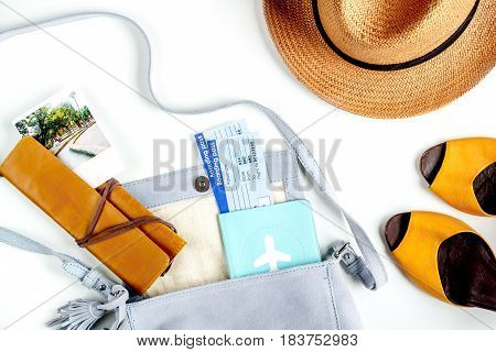 tourist stuff with flight tickets, hat and shoes on white table background top view