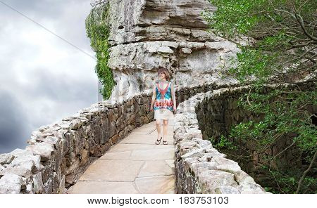 horizontal image of a woman walking down a very high and curving stone walkway beside a cliff in the summer time.
