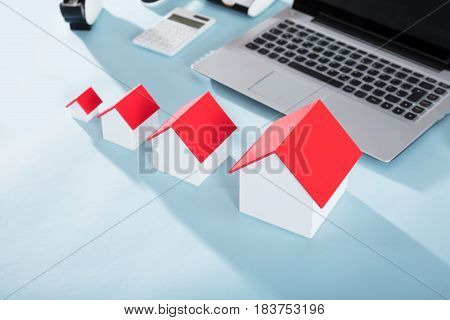 Different Size House Models With Red Roof On Office Desk
