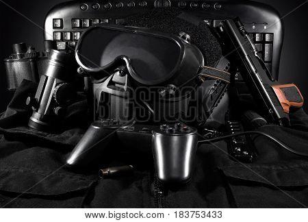 Tactical helmet, gloves, gun, binoculars laying on a jacket with gamepad & keyboard on background.