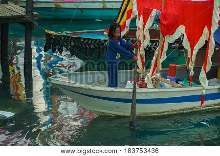 Semporna,Sabah-Apr 22,2017:Sea Bajau girl of Semporna  rowing a boat during Regata Lepa Lepa in Semporna,Sabah,Borneo.Lepa means Boat in the dialect of Sea Bajau people