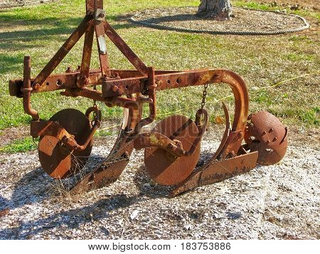 Rusty old plow displayed on bed of sand