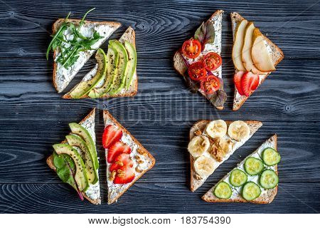 triangle sandwiches set on dark wooden table background top view