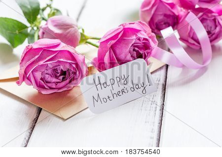 Mother's day gift with peony flowers, envelope and greeting card on wooden table background