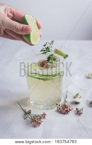 natural nonalcoholic cocktail with herbs and cut lime for summer party on stone desk background