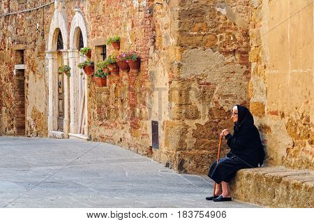 Elderly lady with her memories sitting on a stone bench outside during the siesta in Castelmuzio, Tuscany, Italy - 27 September 2011