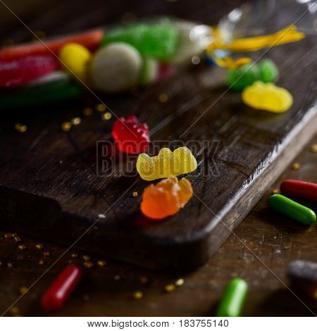 closeup of some candies with different flavors and colors on a rustic wooden chopping board, on a table