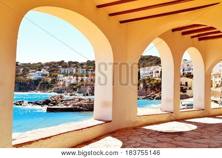 a view of the the Barques Beach and the coast of Calella de Palafrugell, in the Costa Brava, Catalonia, Spain, seen through the arches of the characteristics porticos of its white houses