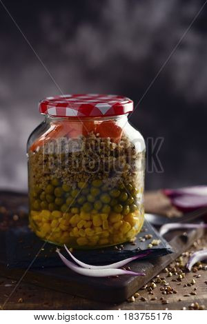 a salad made with sweet corn, green peas, quinoa and carrot served in a mason jar, in different lays, placed on a rustic wooden table
